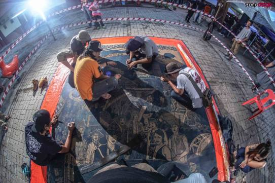 "Pangrok Sulap preparing the woodcut block for ""Sabah Tanah Air-ku"". Photo credit Srap Dsign"
